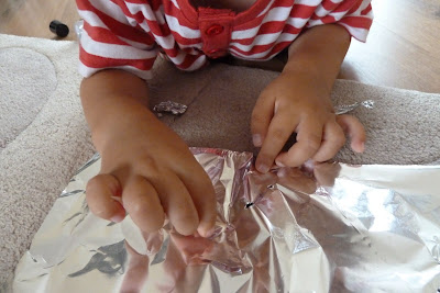 Child playing with tin foil