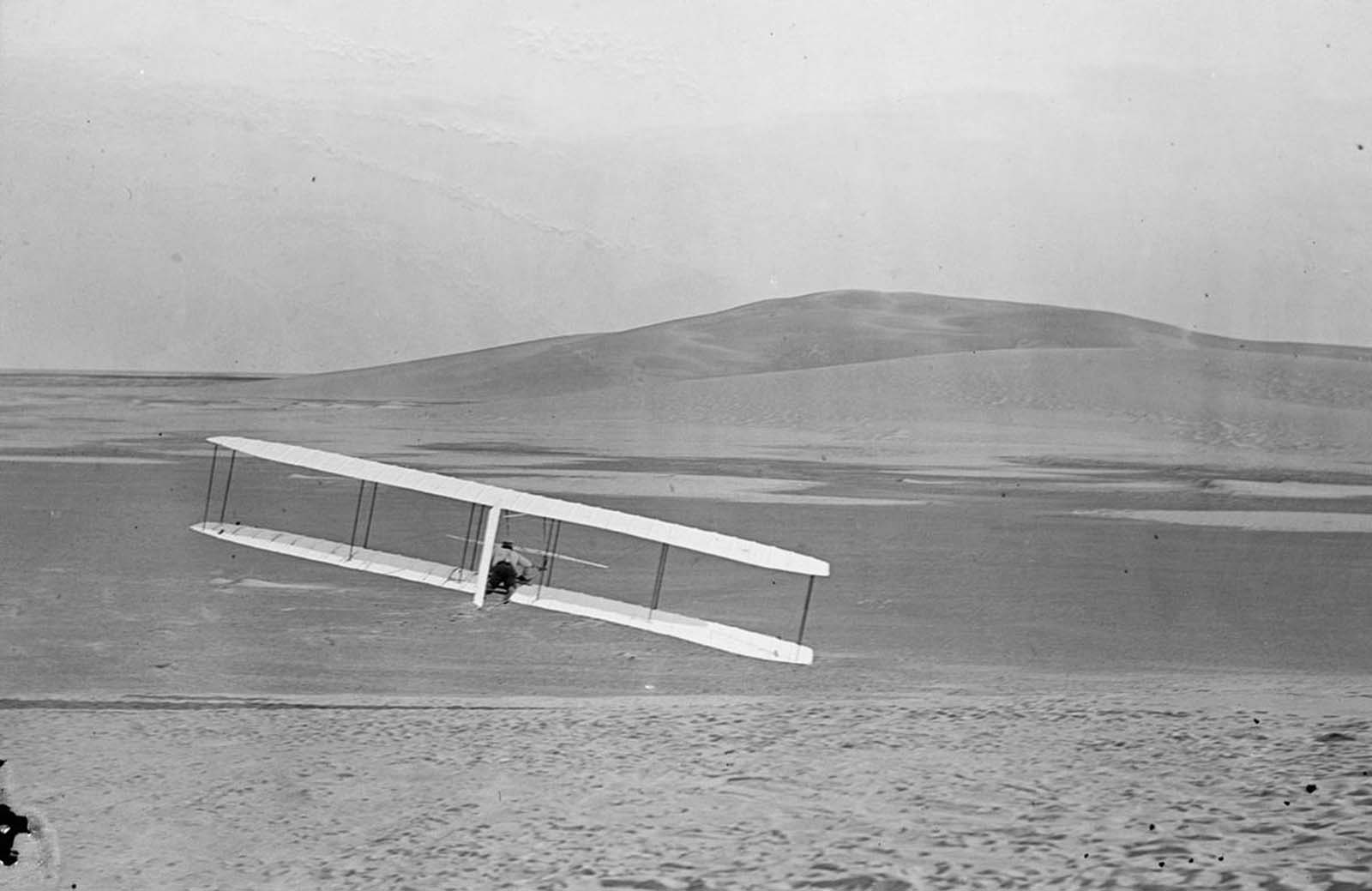 Rear view of Wilbur making a right turn in glide from No. 2 Hill, right wing tipped close to the ground, October 24, 1902.