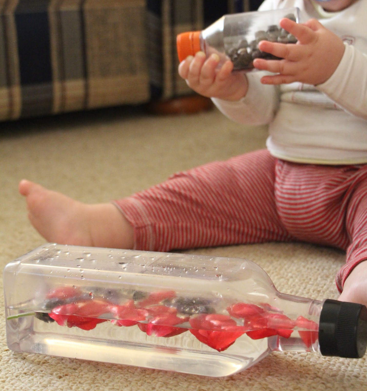 Baby playing with two nature themed discovery bottles