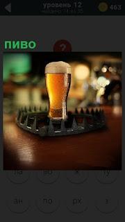 На столе в оригинальной подставке стоит бокал светлого пива