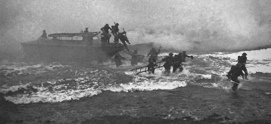 Photo of soldiers in a 1941 WWII beaching exercise. Jack Churchill (far right) leads his unit, sword in hand. Other soldiers jumping from a boat while carrying weapons and ladders to shore. Overstreet and Mad Jack and other stories of pilots. marchmatron.com