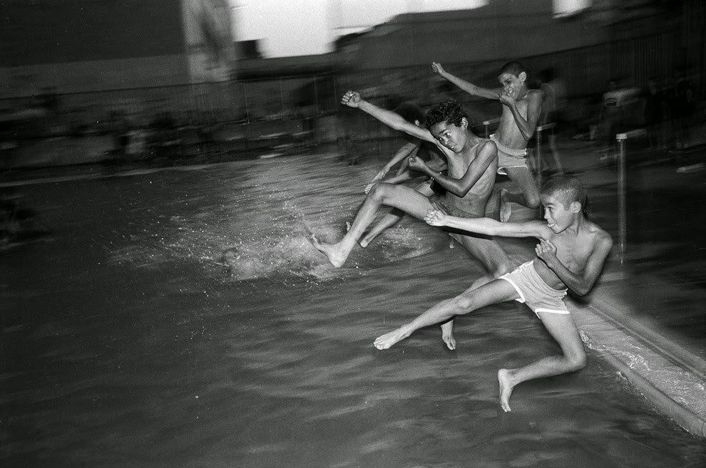 Teenage boys jump into a public swimming pool at night. They climbed over  the fence, 1984.