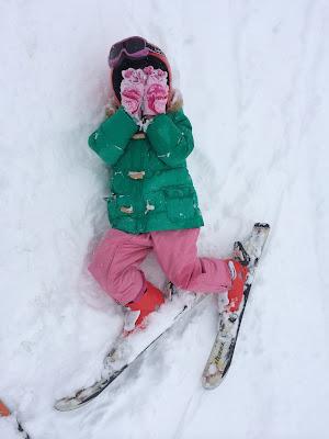 Niña tumbada sobre la nieve con la cara tapada