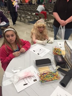 Two young girls sitting at a table doing an acttivity