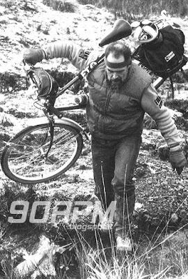 """Fotografia tratta dal libro """"Mountain bike"""": un ciclista vestito con abiti improvvisati trasporta in spalla la bicicletta camminando su un fondo non pedalabile."""