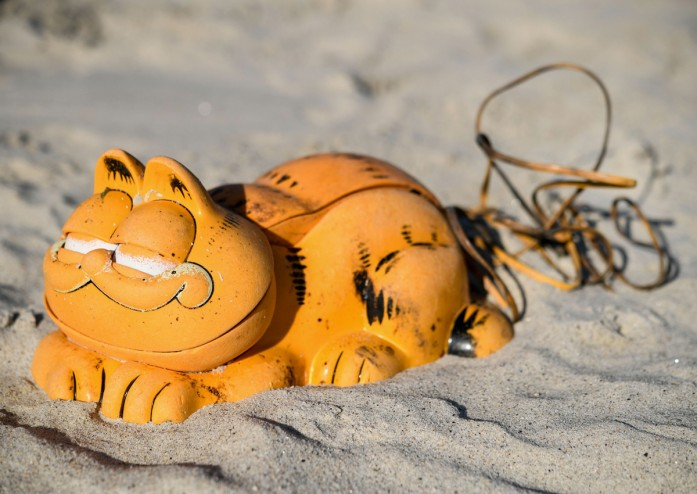 Spare parts of plastic 'Garfield' phones are displayed on the beach in Plouarzel, western France, after being collected from a sea cave by environmental activists.