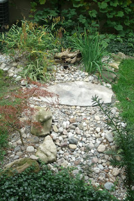 Dry stream bed with river rock, boulders and flagstone bridge by garden muses: a Toronto gardening blog