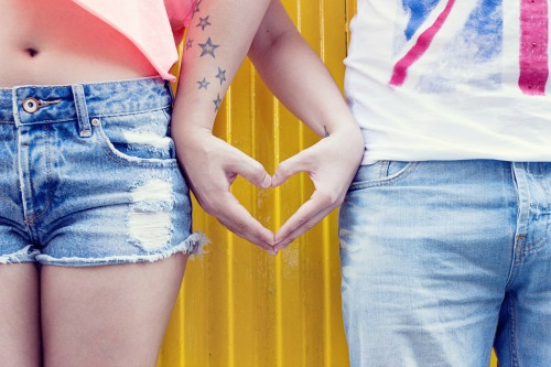 Two people standing next to each other, making a heart shape with their hands