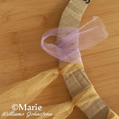 Tying strips of tulle around cardboard