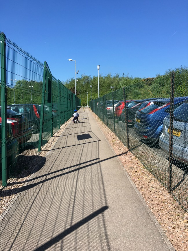 Our-weekly-journal-15th-may-2017-Cardiff-Bay-and-shadows-toddler-on-a-bike-between-chain-fence-and-parked-cars