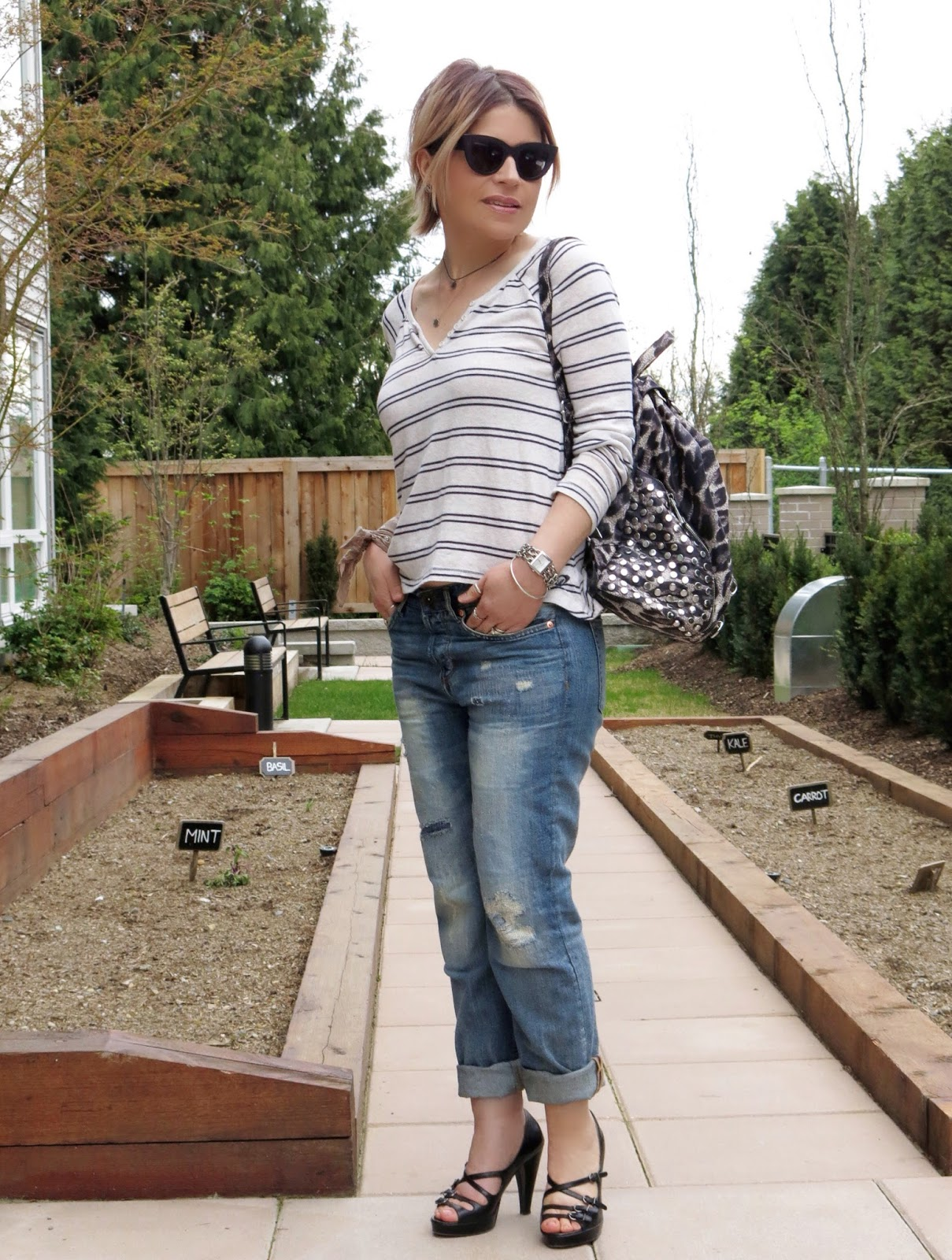 styling boyfriend jeans with a striped henley, strappy platform heels, and cat-eye sunglasses