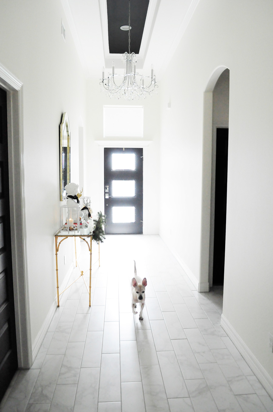 Bright white foyer, black glass front door, bamboo gold console table and alabaster walls.