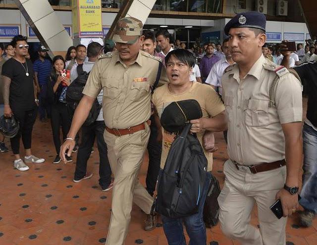 Policemen detain a GJM activist, Yogendra Pradhan, at Bagdogra airport