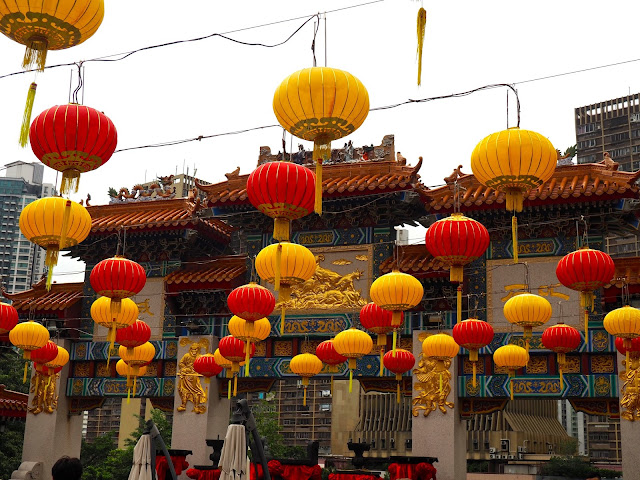 Red & yellow Chinese lanterns hanging in the courtyard of Sik Sik Yuen Wong Tai Sin Temple, with the ornamental archway in the background | Hong Kong