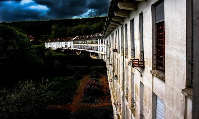 photo de l immense sanatorium vu de l'extérieur avec un ciel sombre à l'orage