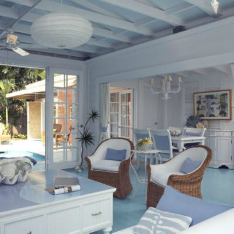 Coastal cottage living room with wicker chairs, light blue painted floor