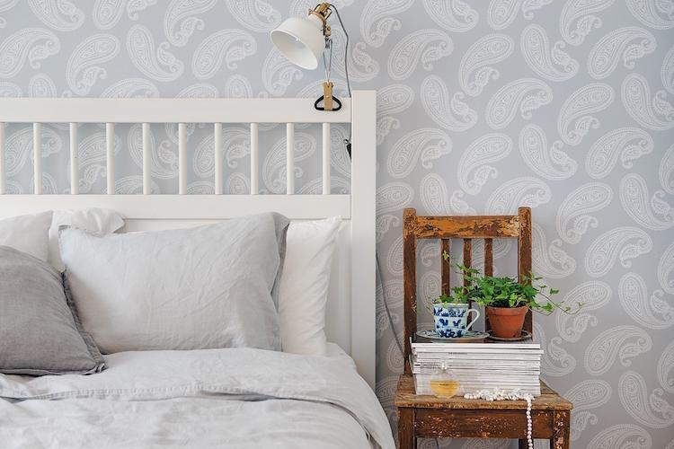 dormitorio con papel pintado y silla antigua por mesita
