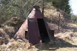 Am Rande des Steinbruchs steht ein ehemaliger, kegelförmiger Sprengbunker. Er ist verrostet.