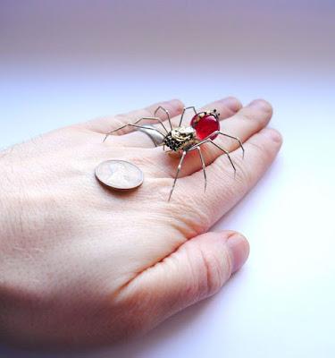 Araña robot hecha con partes de bombillo color rojo y material reciclado