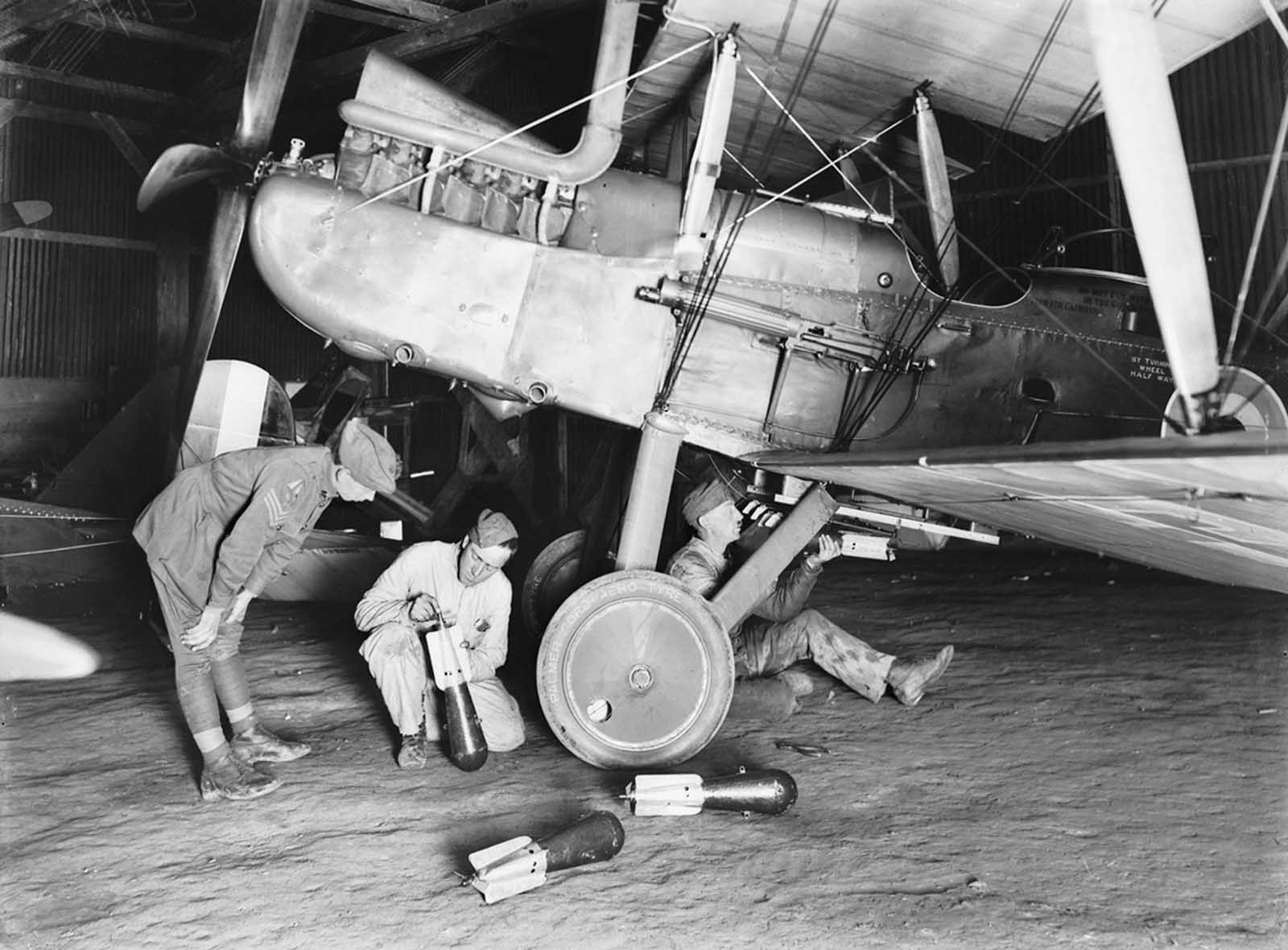 An unidentified member of the 69th Australian Squadron, later designated No. 3 Australian Flying Corps, fixes incendiary bombs to an R.E.8 aircraft at the AFC airfield north west of Arras. The entire squadron was operating from Savy (near Arras) on October 22, 1917, having arrived there on September 9, after crossing the channel from the UK.