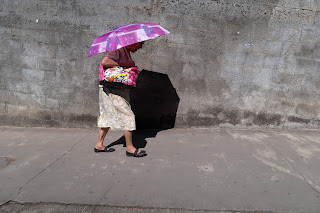 Woman with umbrella on sidewalk in Puriscal.