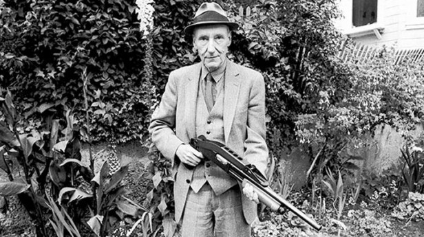 William S. Burroughs holding a shot gun in a garden, looking at camera.