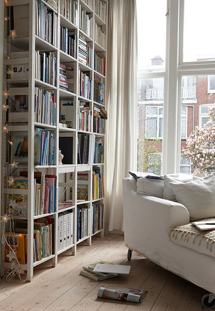Beautiful white bookshelves with white string of fairy lights