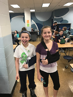 Two 6th grade students smiling despite their injuries