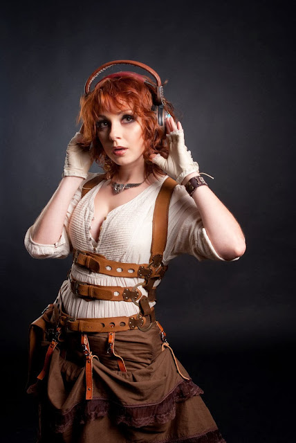 Redhead Steampunk Cosplayer wears skirt, blouse, harness and headphones