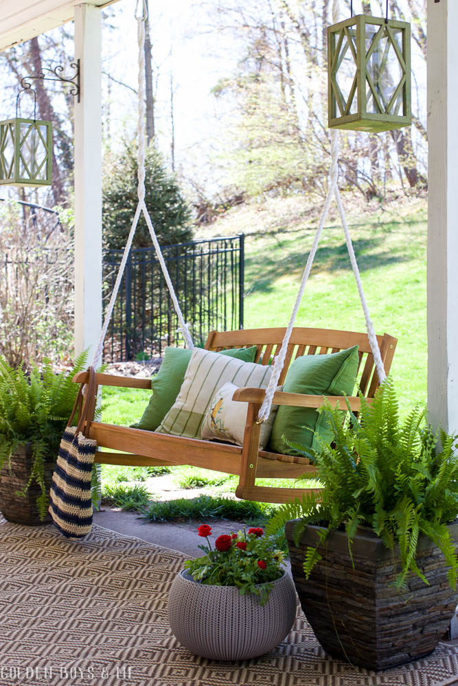 Spring covered patio refresh with porch swing and potted ferns