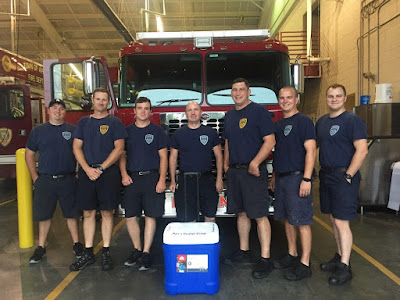 Firemen at Fire Station 4 pose by truck with cooler.