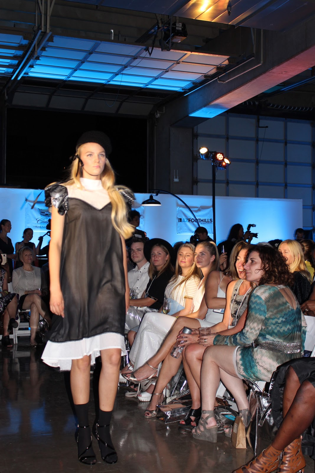 The model is strutting down the runway in a sheer black dress, while wearing a hat similiar to an English guard hat.