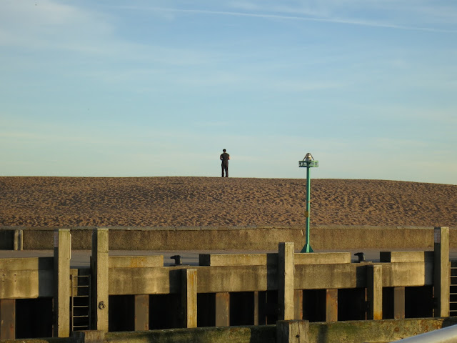 Man standing on Chesil Beach at West Bay in Dorset, looking out to sea above harbour.