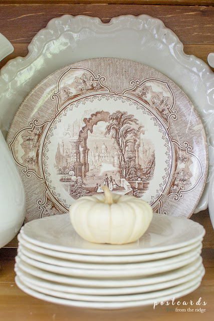 small white pumpkin on stack of white dishes with brown and white dish behind it