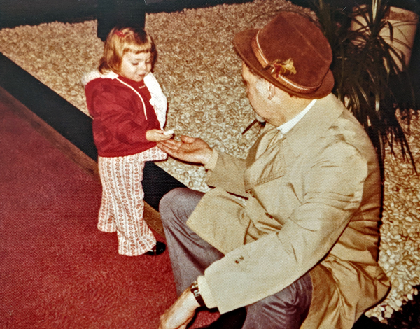 image of me as a baby standing next to a rock feature at an airport with my grandfather, who is holding out his hand while I place rocks from the feature into his palm