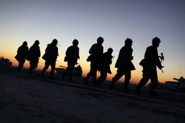 Image Attribute: Soldiers of the People's Liberation Army (PLA) Marine Corps march during a military drill as the sun rises at a military base in Taonan, Jilin province January 28, 2015. REUTERS/China Daily