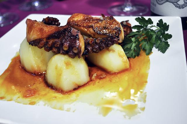 sobre patatas tentáculos de pulpo braseado, una hoja de perejil adorna el plato