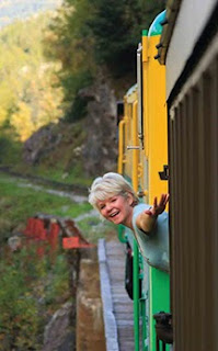Photo of Brenda Wilbee leaning out the White Pass Train, taken by Blake Kent