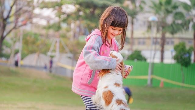 seorang anak perempuan memeluk anjing miliknya