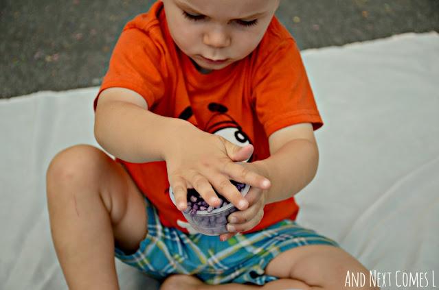 Toddler playing with sensory bean bin