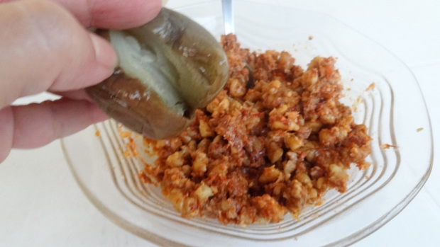 Holding the eggplant with fingers and nut garlic mixture in a plate