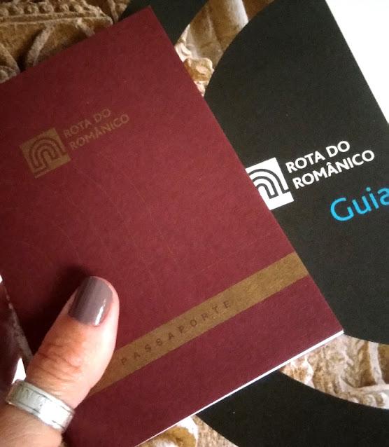 mão segurando o passaporte e o guia da Rota do Românico