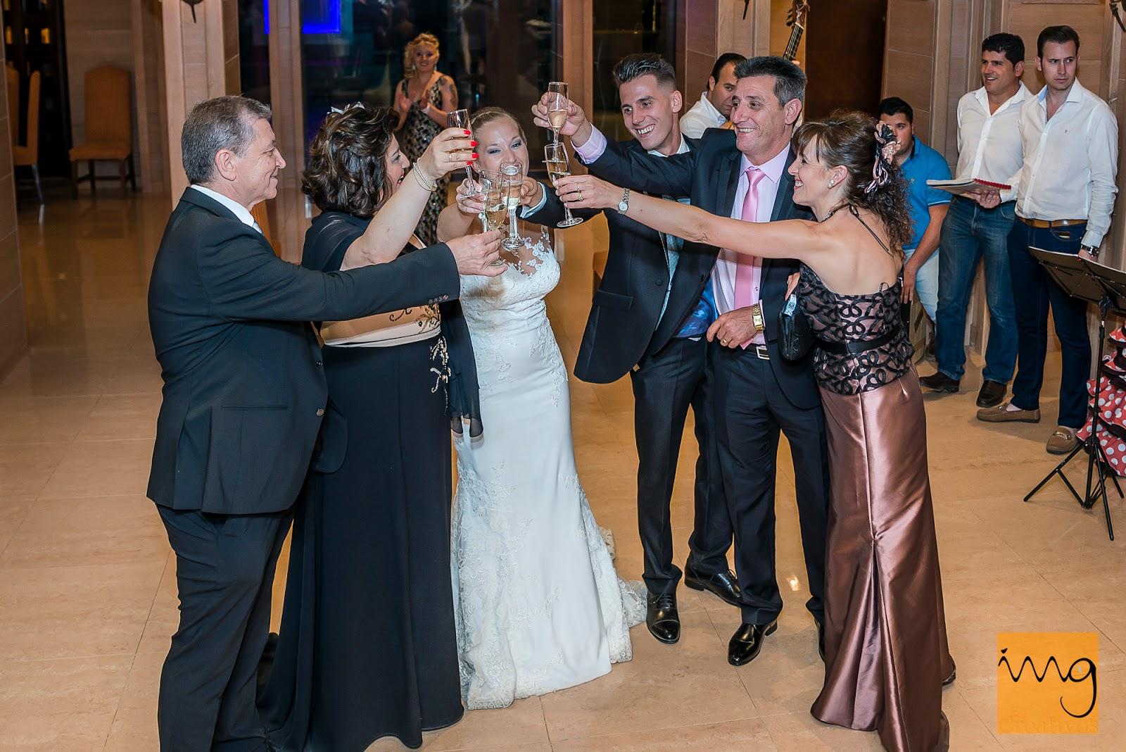 Fotografía de los novios y su familia haciendo un brindis en el restaurante en Granada