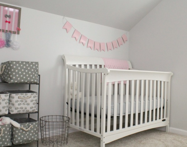 Gray white and light pink nursery for a baby girl- Gray canvas and rope decorative storage baskets, metal wire laundry basket, white crib from Target with polka dot fitted sheet and pink flag banner decoration