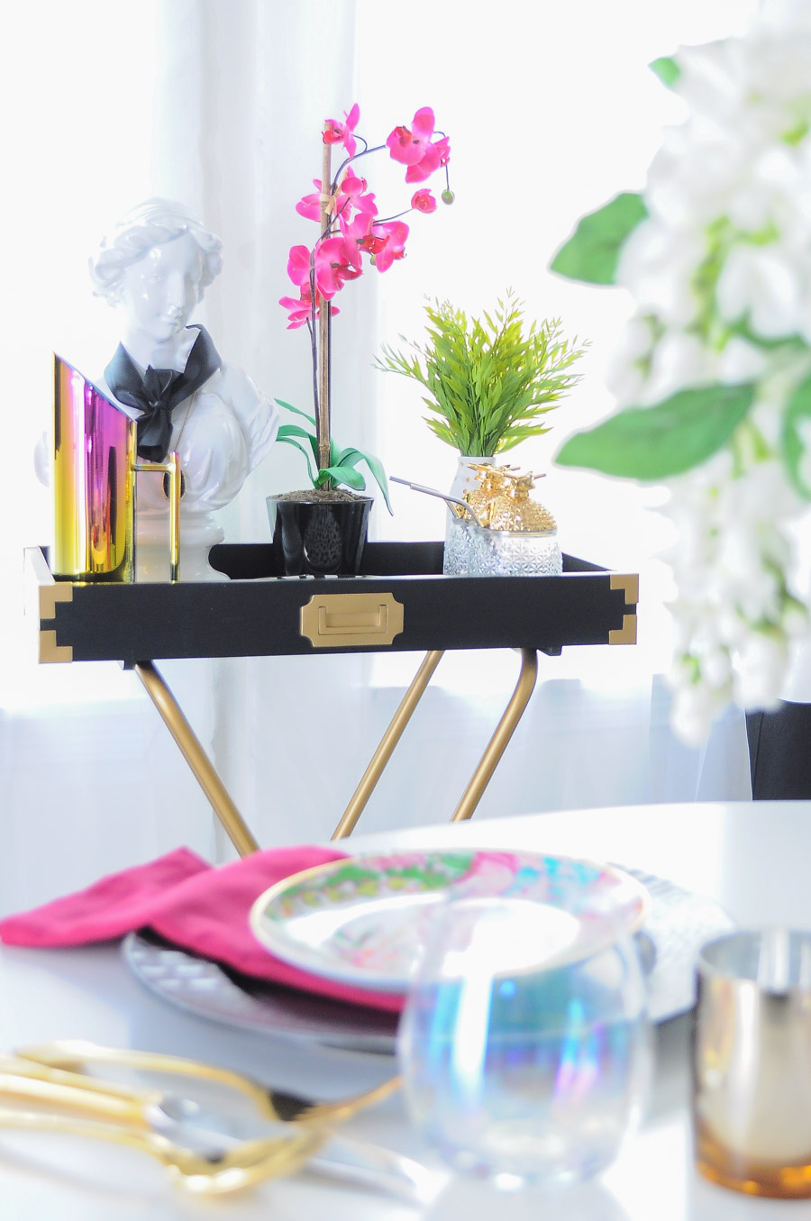 A black and gold campaign valet stand styled to perfection with bold, colorful and glam decor accents.