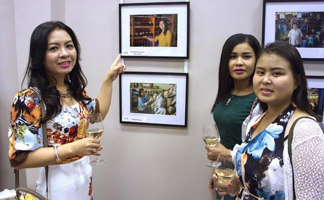 Propriétaire et employées d'Ellis Wine Shop and Soft Drinks devant leur photographie en compétition