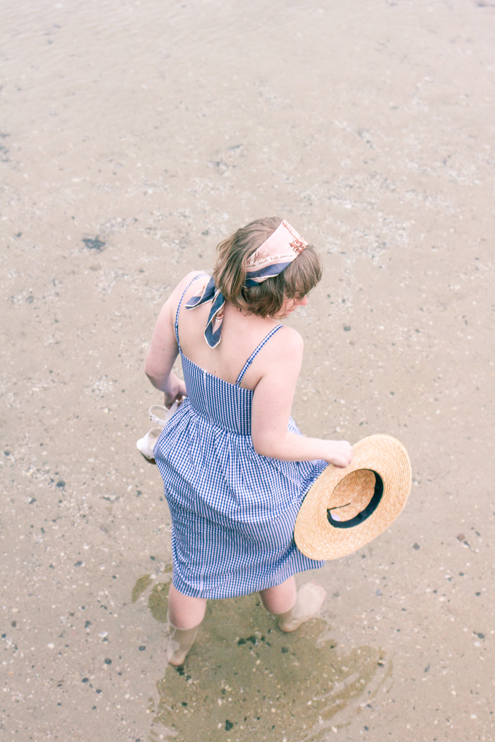 @findingfemme wears Seed Heritage blue gingham summer dress as the beach with straw boater