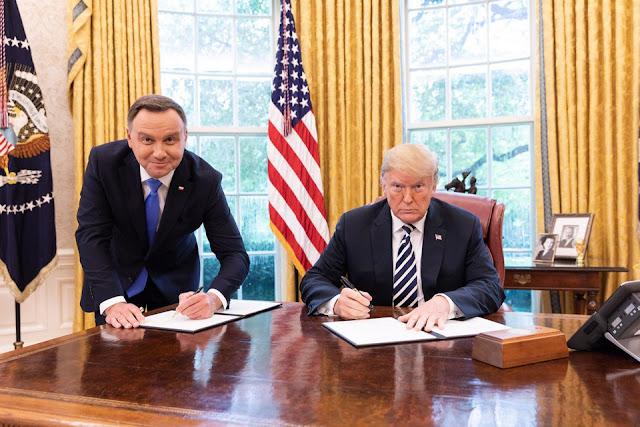 Prezydent Donal Trump i Prezydent Andrzej Duda  podpisują umowę przy biurku
