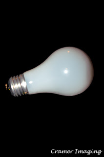 Photograph of a single incandescent light bulb on its side on a black background by Cramer Imaging