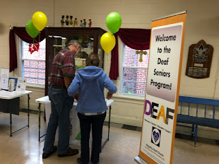 "two people look at a table,  on their right is a banner, ""Welcome"""